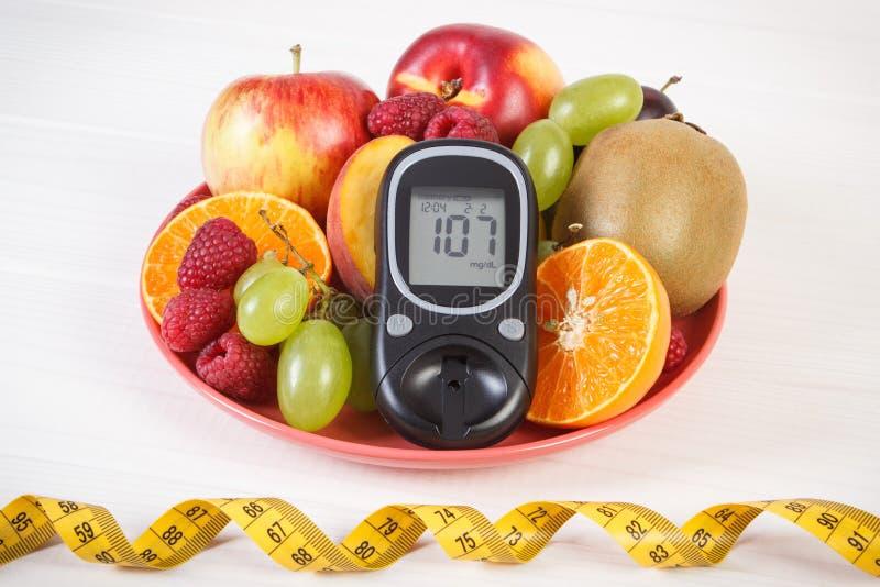 Glucometer nya frukter på plattan och cm, sockersjuka och sund näring royaltyfri bild