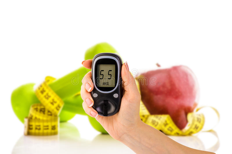 Glucometer para o nível da glicose e o alimento biológico saudável em um fundo branco Conceito do diabetes imagem de stock
