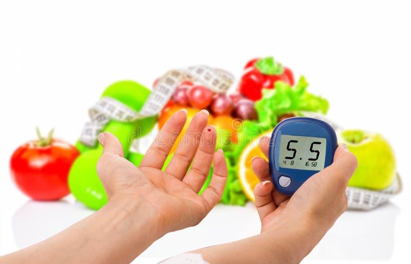 Glucometer pour le niveau de glucose et l'aliment biologique sain sur un fond blanc Concept de diabète photo stock