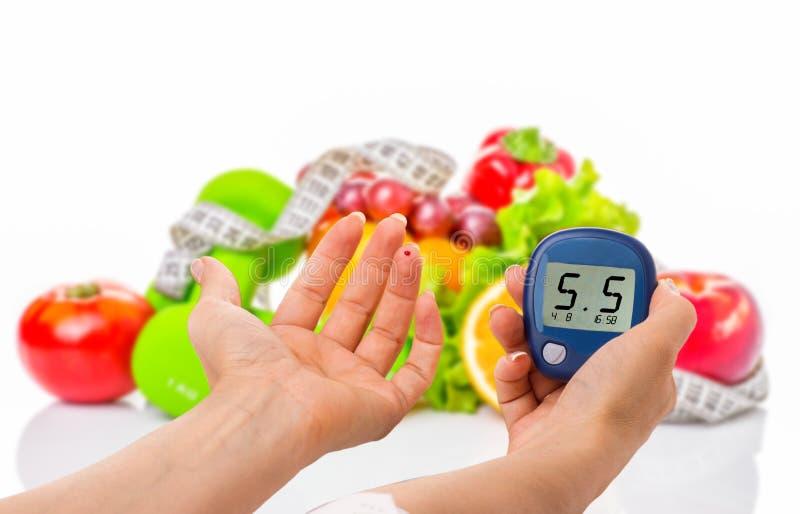 Glucometer pour le niveau de glucose et l'aliment biologique sain sur un fond blanc Concept de diabète photographie stock