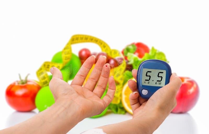 Glucometer pour le niveau de glucose et l'aliment biologique sain sur un fond blanc Concept de diabète photos libres de droits