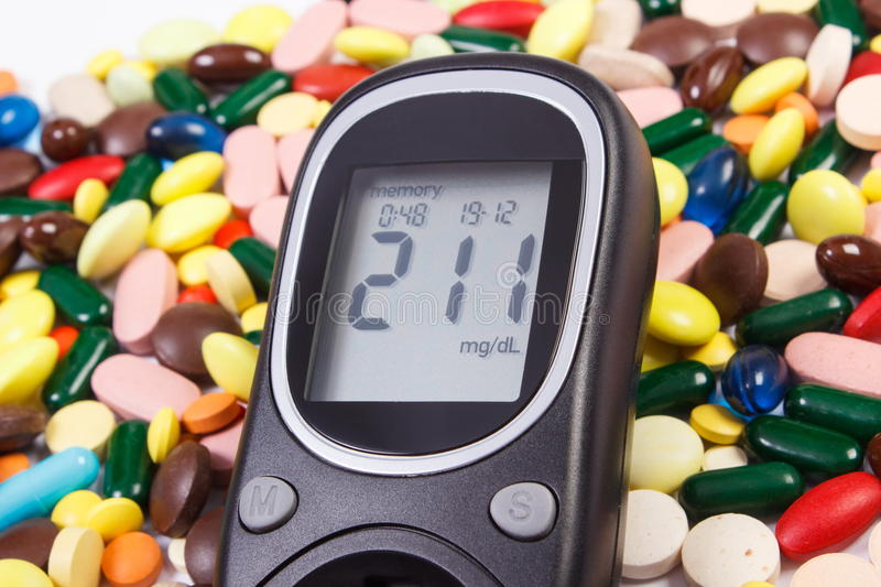 Glucometer with result sugar level and heap of medical pills and capsules, diabetes, health care concept royalty free stock photo