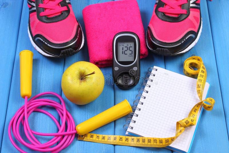 Glucometer, sportschoenen, verse appel en toebehoren voor fitness op blauwe raad, exemplaarruimte voor tekst royalty-vrije stock fotografie
