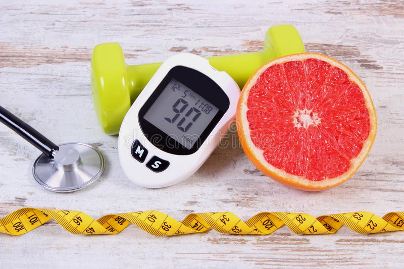 Glucometer, stethoscope, fresh grapefruit and dumbbells for fitness, diabetes, healthy lifestyles. Glucose meter with result measurement sugar level, medical stock photos
