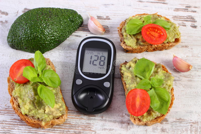 Glucometer und frisch Sandwiche mit Paste der Avocado, des Diabetes, des gesunden Lebensmittels und der Nahrung stockfotos