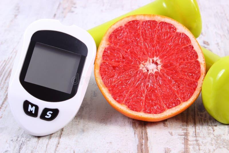 Glucometer voor het meten van suikerniveau, verse grapefruit en domoren voor geschiktheid, gezond levensstijlenconcept stock foto's