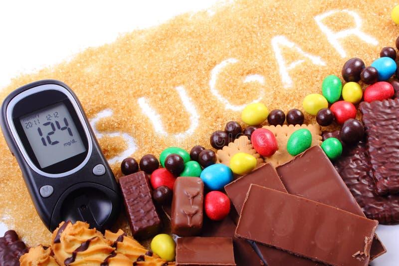 Glucometer, zucchero bruno della canna e molti dolci immagini stock