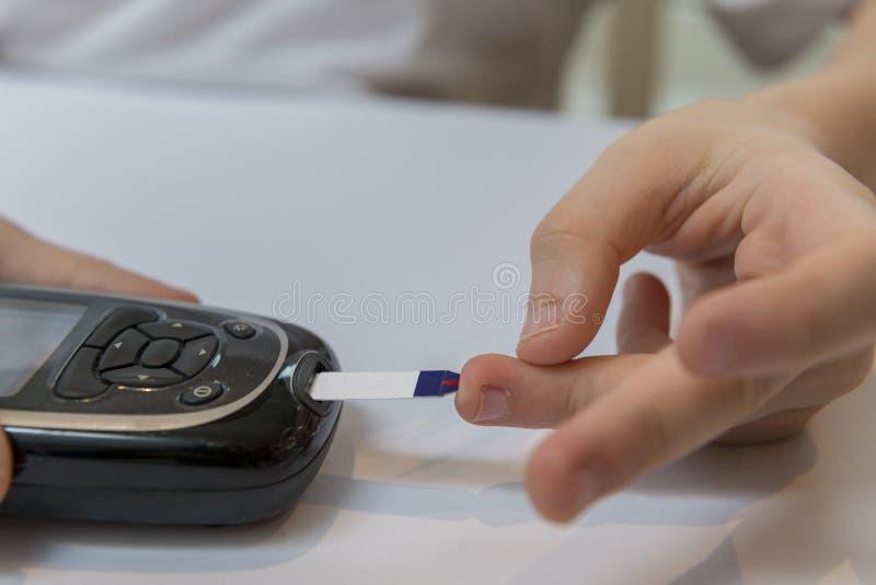 Glucose de mesure de garçon ou suger de sang photos stock