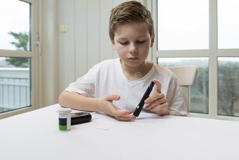 Glucose de mesure de garçon ou suger de sang images stock