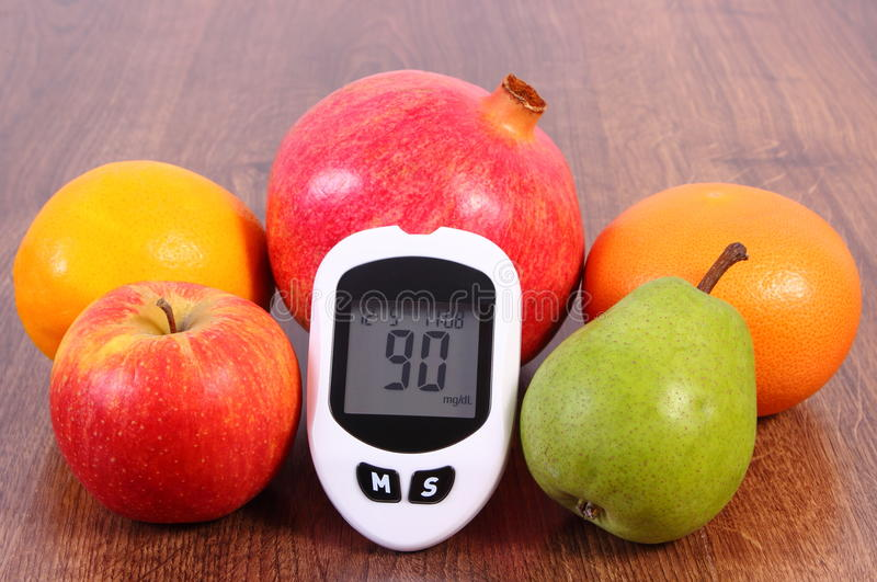 Glucose meter with fresh fruits, diabetes and healthy nutrition. Glucose meter with good result sugar level and fresh ripe fruits, concept of diabetes, healthy royalty free stock images
