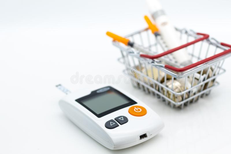 Glucose meter and injection needle on cash basket , image use for health care concept.  royalty free stock photography