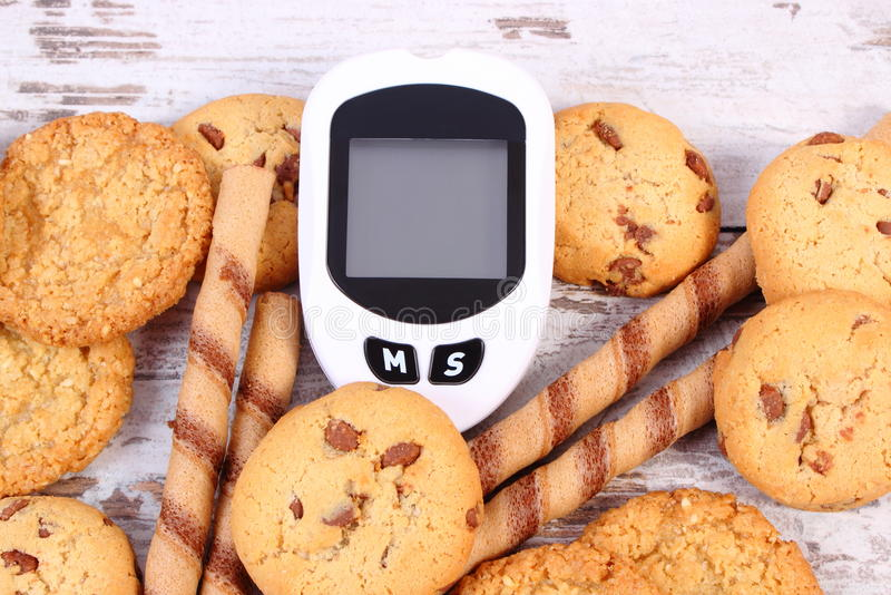 Glucosemeter om suikerniveau en hoop van koekjes te meten, concept vermindering die snoepjes eten royalty-vrije stock foto
