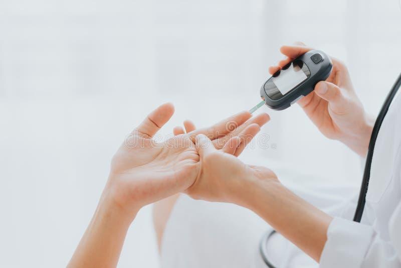 Glucosmeter d'utilisation de docteur vérifiant le taux du sucre dans le sang images stock