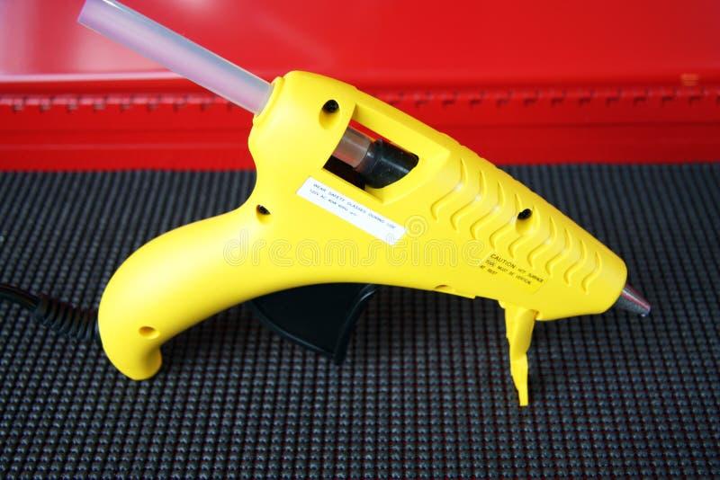 Glue Gun. Standing yellow glue gun on a texture black surface stock images