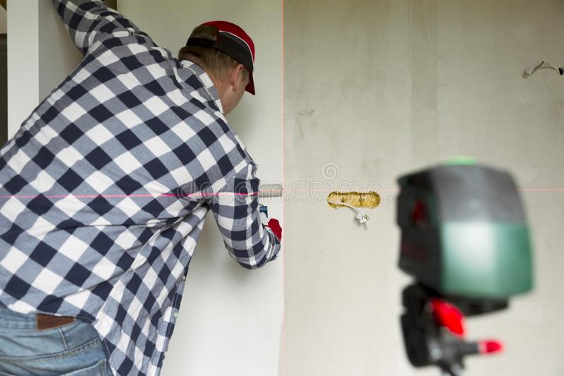 Glueing wallpapers at home. Young man, worker is putting up wallpapers on the wall. Home renovation concept.  royalty free stock photos