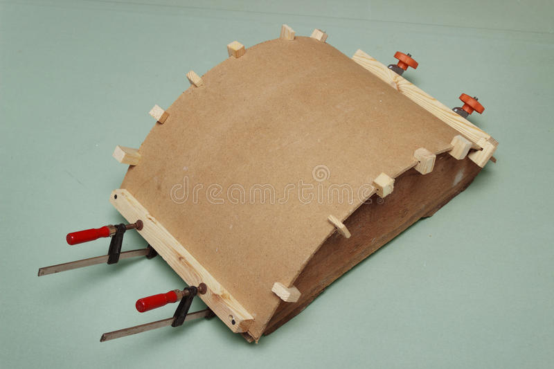 Gluing the arch of hardboard with the use of forms stock image