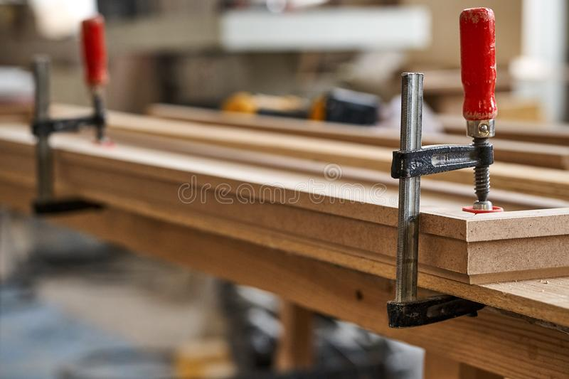 Gluing and clamping crown molding. Production of wood furniture. Furniture manufacture. Close-up. Gluing and clamping crown molding in workshop. Furniture royalty free stock photo