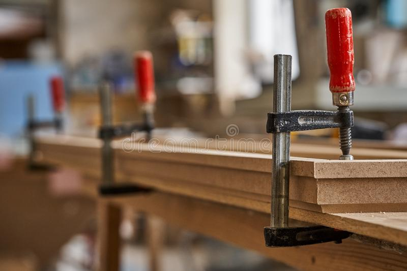 Gluing and clamping crown molding. Production of wood furniture. Furniture manufacture. Close-up. Gluing and clamping crown molding in workshop. Furniture royalty free stock photography