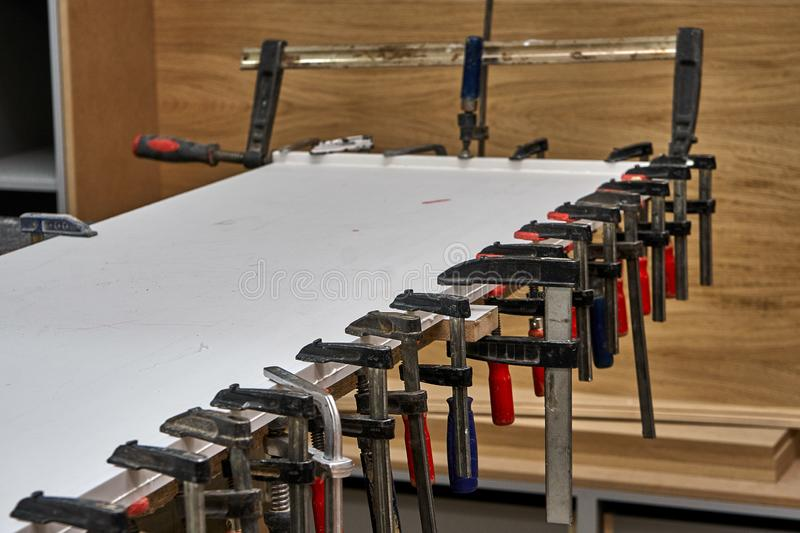 Gluing and clamping table top of acrylic stone. Production of wood furniture. Furniture manufacture. Close-up. Gluing and clamping table top of acrylic stone in royalty free stock image