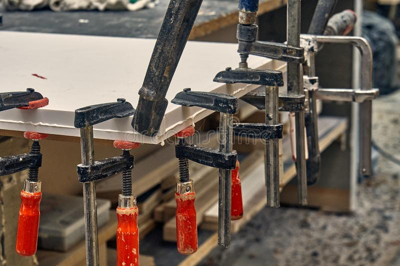 Gluing and clamping table top of acrylic stone. Production of wood furniture. Furniture manufacture. Close-up. Gluing and clamping table top of acrylic stone in royalty free stock photos