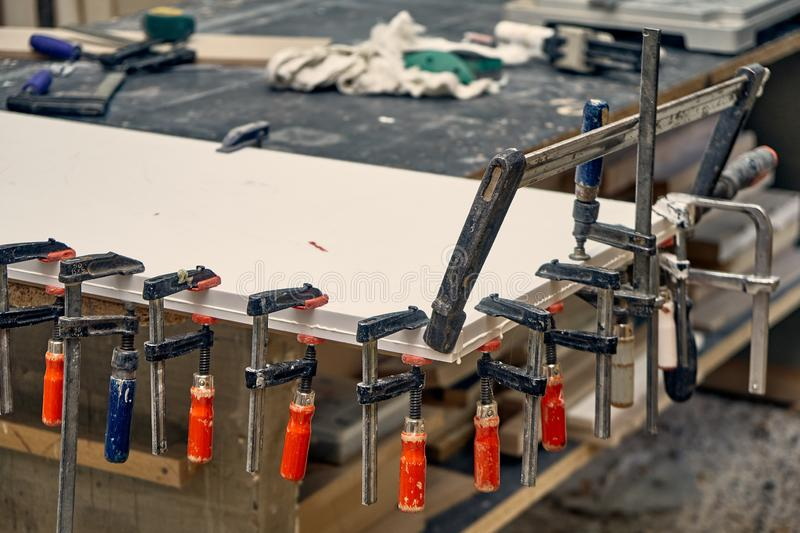 Gluing and clamping table top of acrylic stone. Production of wood furniture. Furniture manufacture. Close-up. Gluing and clamping table top of acrylic stone in stock photo