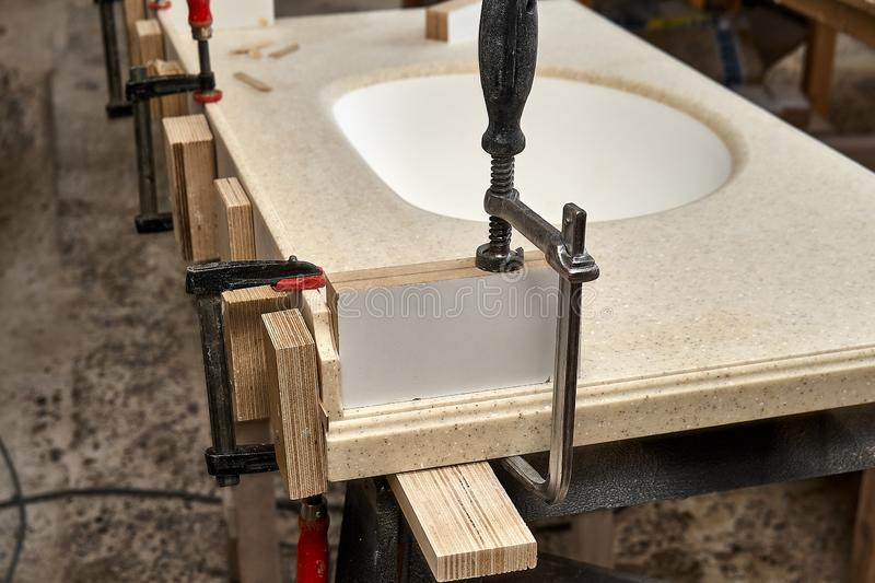 Gluing and clamping table top of acrylic stone with acrylic sink. Production of wood furniture. Furniture manufacture. Gluing and clamping table top of acrylic stock photography