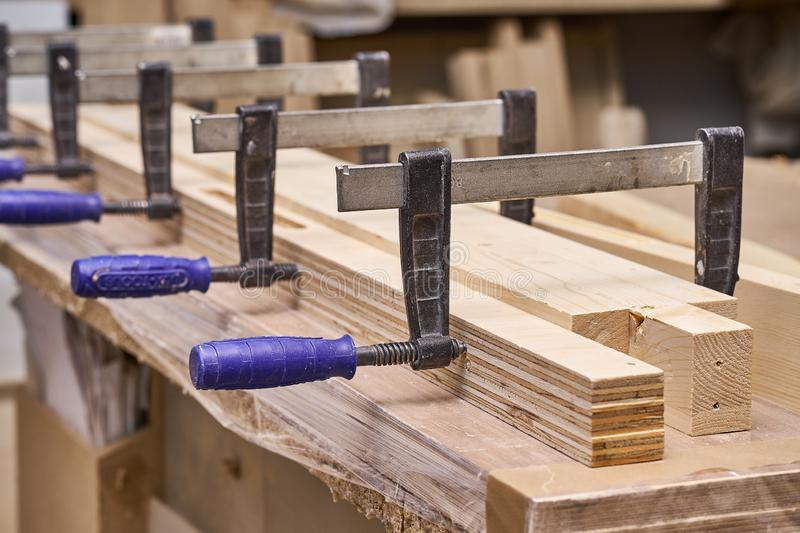 Gluing and clamping wooden detail. Production of wood furniture. Furniture manufacture. Close-up. Gluing and clamping wooden detail in workshop. Furniture stock photo