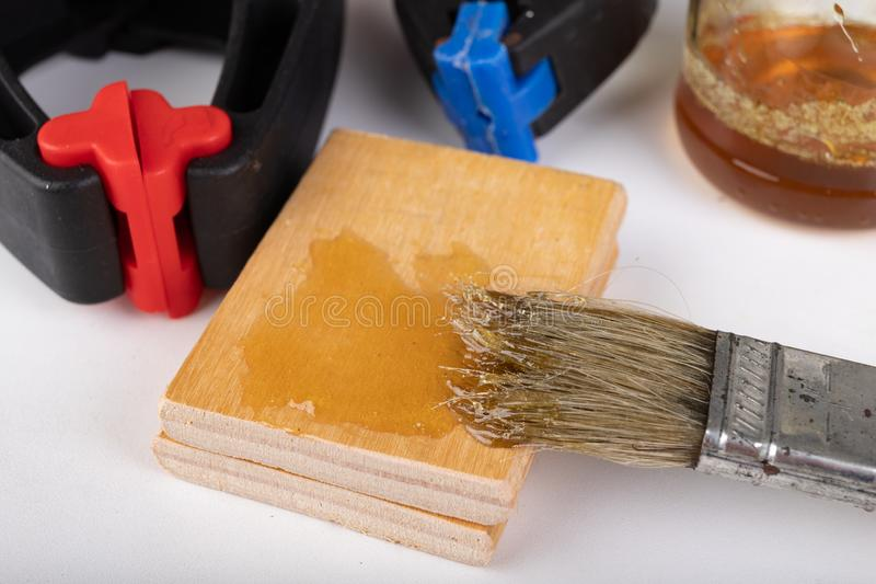 Gluing wood with waterproof adhesive. Pieces of wood pressed together with carpentry clamps. Place - carpentry workshop, art, artisan, assemble, c-clamp royalty free stock image