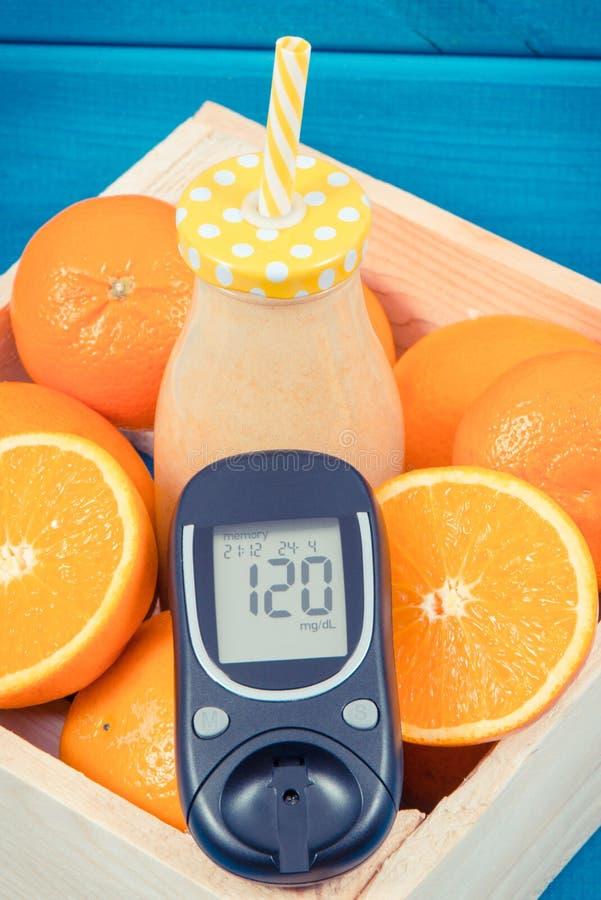 Glukosmeter för att kontrollera sockernivån och sund coctail eller fruktsaft från citrusfrukter Sockersjuka bantar och bantningen royaltyfri fotografi