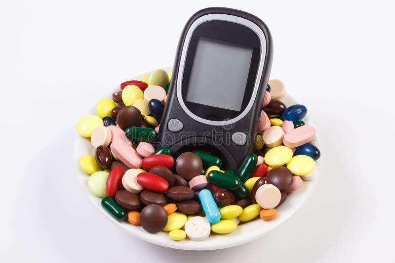 Glukosmeter med högen av medicinska preventivpillerar och kapslar, sockersjuka, hälsovårdbegrepp royaltyfri fotografi