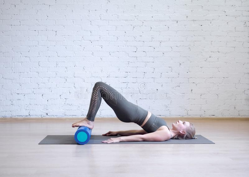 Gluteal bridge on foam roller. Young caucasian woman doing pilates with special equipment in fitness studio. stock images
