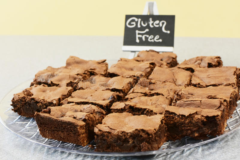 Gluten Free Brownies. A plate full of gluten free chocolate fudge brownies with a little chalkboard sign that says gluten free on it in white chalk royalty free stock photography