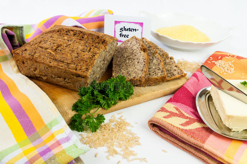 Gluten-free diet. Wooden board with homemade, gluten-free wholemeal bread from rice and corn, served with butter, isolated stock photography