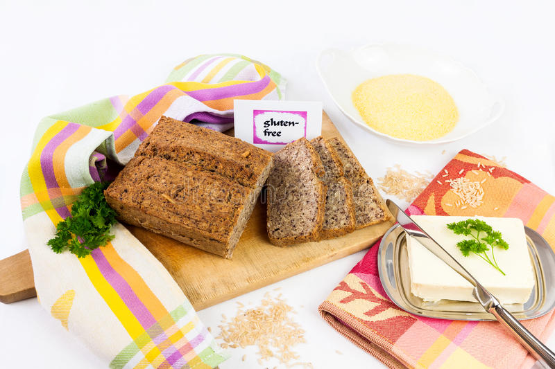 Gluten-free diet. Wooden board with homemade, gluten-free wholemeal bread from rice and corn, served with butter, isolated royalty free stock photos