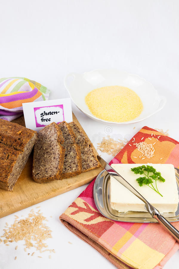 Gluten-free diet. Wooden board with homemade, gluten-free wholemeal bread from rice and corn, served with butter, isolated, copy space royalty free stock photo
