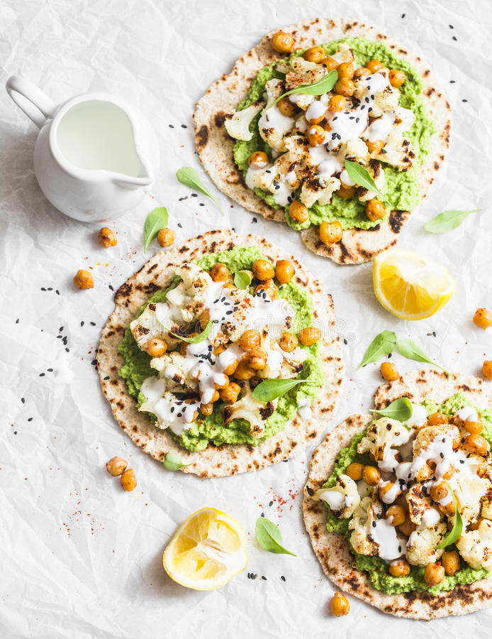 Gluten free flatbread with roasted chickpeas, cauliflower and avocado dip on a light background, top view. Healthy vegetarian food stock image