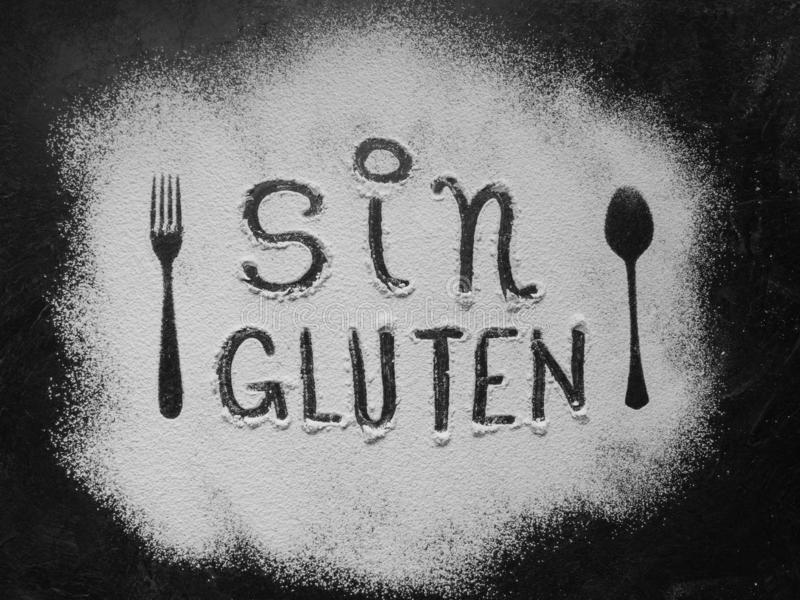 Gluten free flour with text gluten free in Spanish language with spoon and fork silhouette made with flour on dark texture royalty free stock image