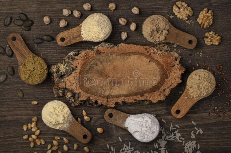 Gluten free flours in wooden spoons royalty free stock photography