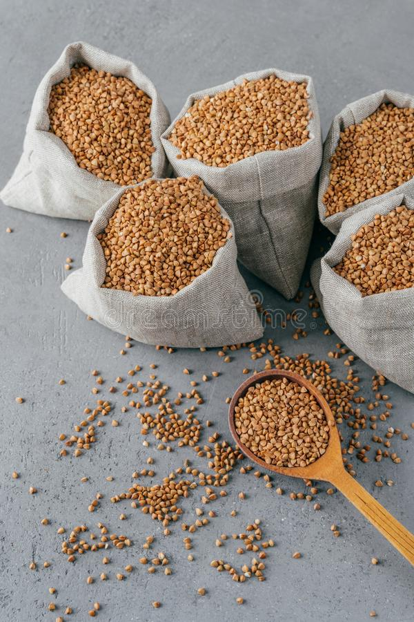 Gluten free product. Vertical shot of dry brown buckwheat for vegetarians. Sacks with cereals. Wooden spoon near. Heathy eating. Concept stock photography