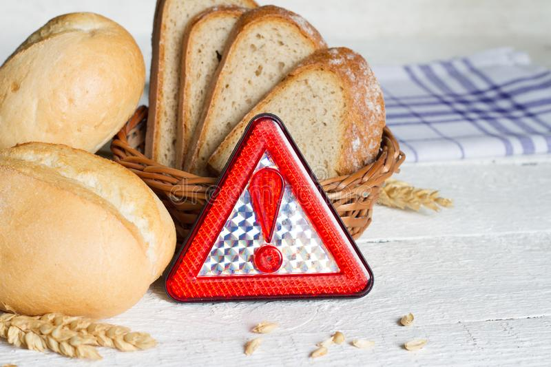 Gluten intolerance with bread wheat and warning sign on white planks royalty free stock images