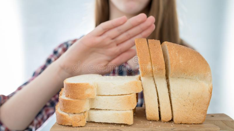 Gluten intolerance concept. Young girl refuses to eat white bread - shallow depth of field royalty free stock photography