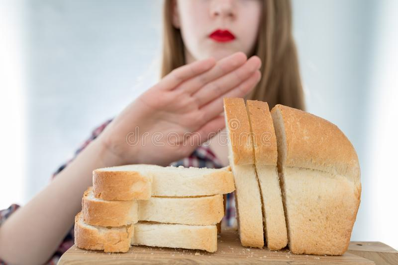 Gluten intolerance concept. Young girl refuses to eat white bread - shallow depth of field royalty free stock photo