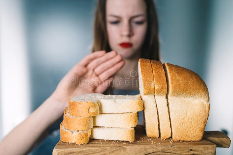 Gluten intolerance and diet concept. Young girl refuses to eat bread stock image