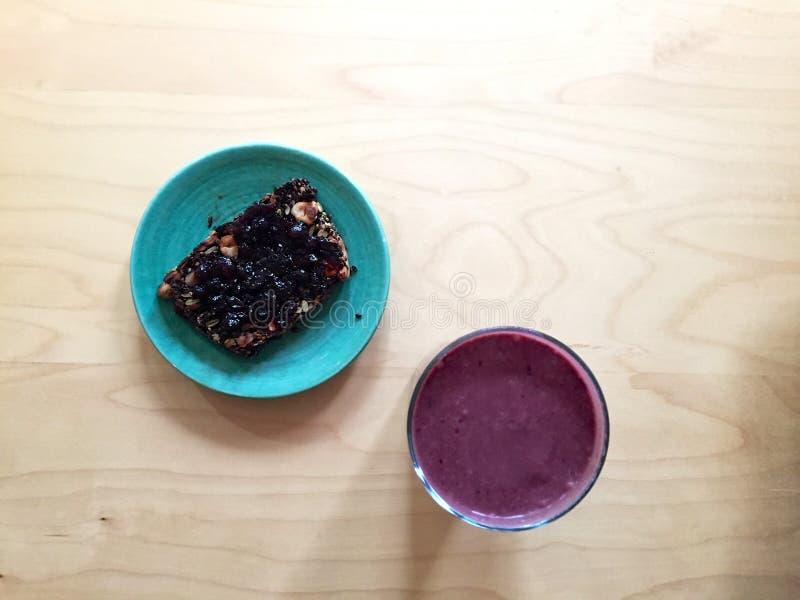 Gluten-vrij brood met jam en roze smoothie op lijst stock foto's