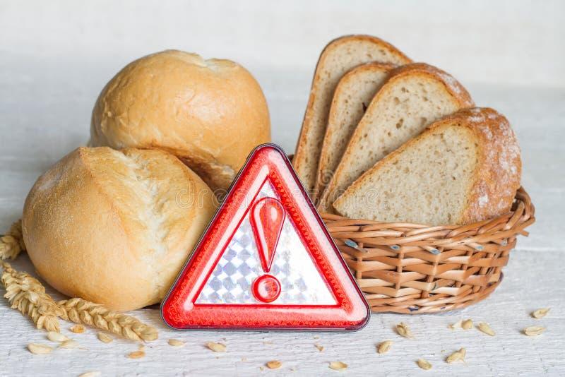 Glutenintolerans med brödvete och varningstecken på vita plankor royaltyfri bild