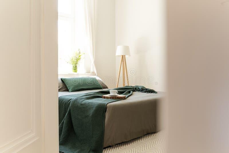 Gluur door een open deur op een bed gekleed in grijs en groen linnen, hoofdkussens en een deken in een binnenland van de eco vrie stock afbeeldingen
