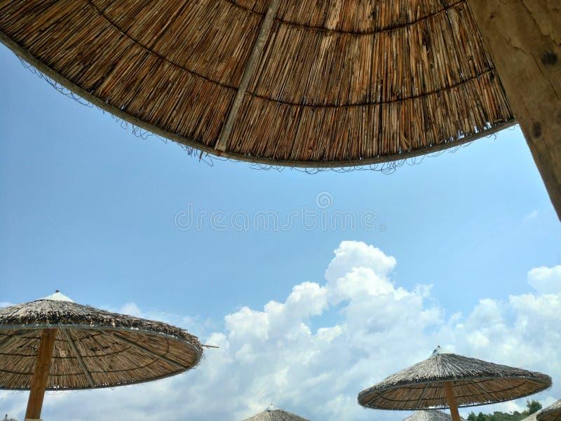 glWicker plażowi parasole pod niebieskim niebem z chmurami, Halkidiki Grecja obrazy royalty free