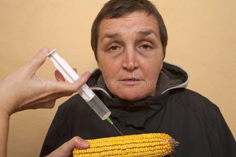GMO corn. Genetically modified organism, ill woman with GMO corn cob royalty free stock photography