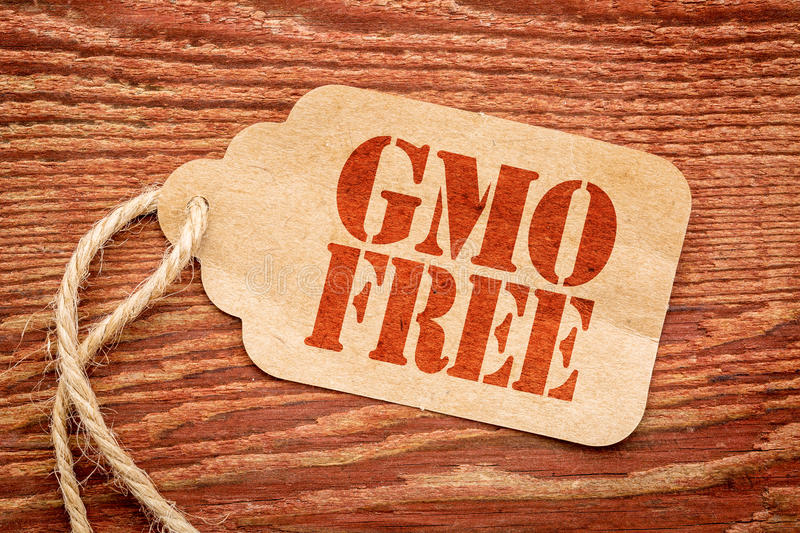GMO free sign on paper price tag. GMO free sign - a paper price tag against rustic red painted barn wood royalty free stock images