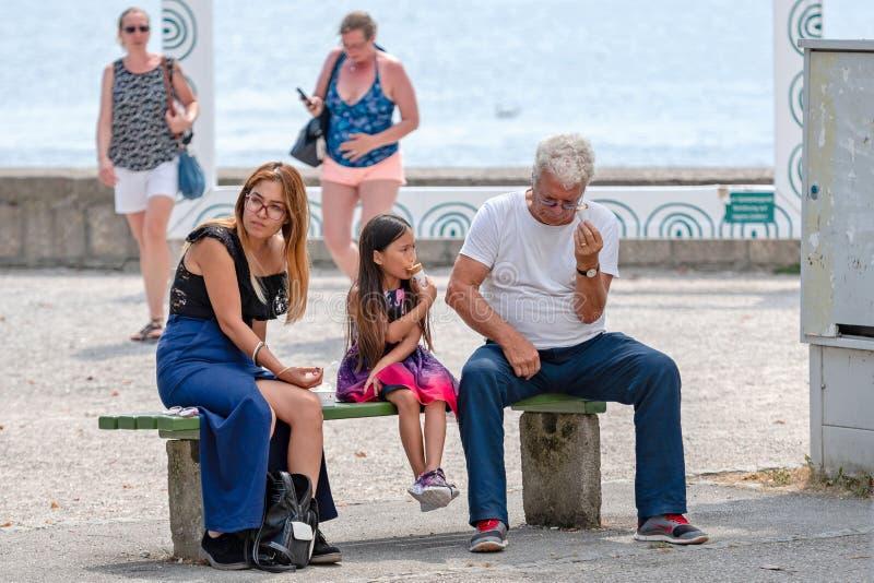 GMUNDEN, ÁUSTRIA, - 3 DE AGOSTO DE 2018: A mulher, o homem e a menina estão sentando-se no banco e estão comendo-se o gelado imagem de stock royalty free
